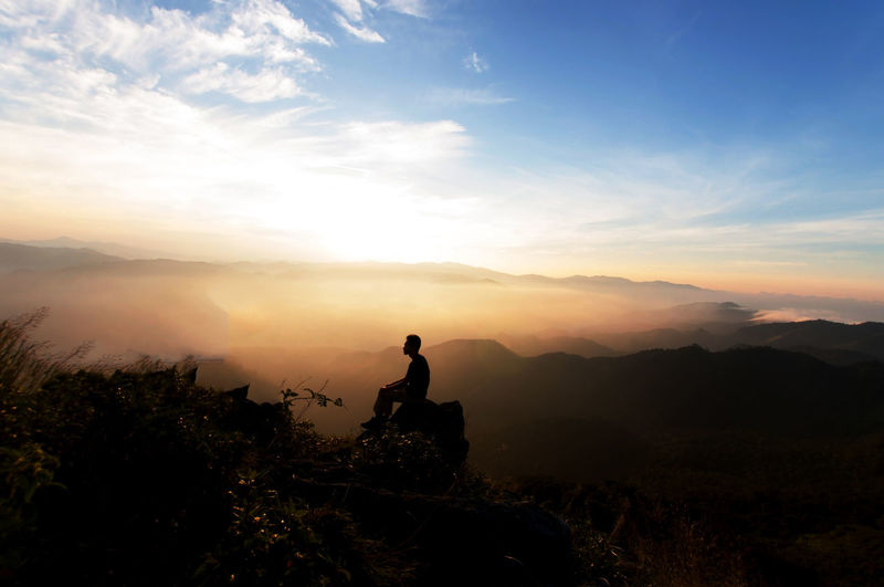 Silhouette Man Sitting On Rock By Landscape Against Sky During Sunset