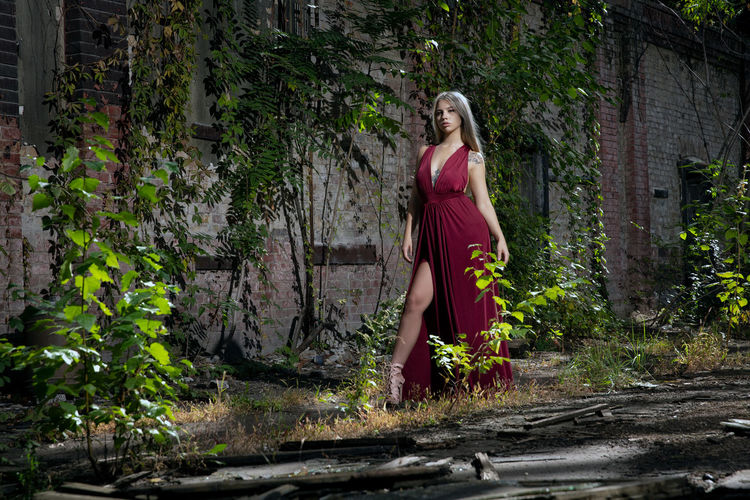 One Person Young Adult Fashion Young Women Plant Lifestyles Standing Full Length Dress Leisure Activity Beauty Women Clothing Adult Hair Real People Day Beautiful Woman Hairstyle Outdoors Contemplation Red Dress Yard Abandoned Places Abandoned Buildings
