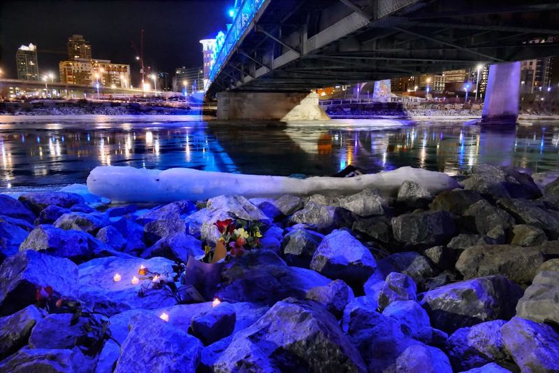 Memorial for a dead man. Under The Bridge Memorial Candles Remembrance Purple Flowers Riverside Bow River Cityscape Riverfront Coloured Reverence Photojournalist - 2016 EyeEm Awards