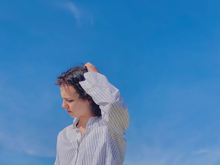 Low angle portrait of young woman standing against blue sky