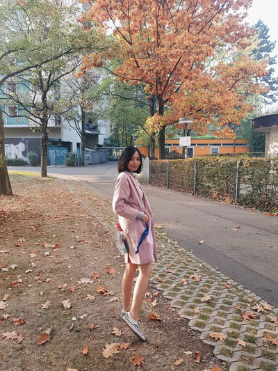 Full length of woman standing by tree during autumn