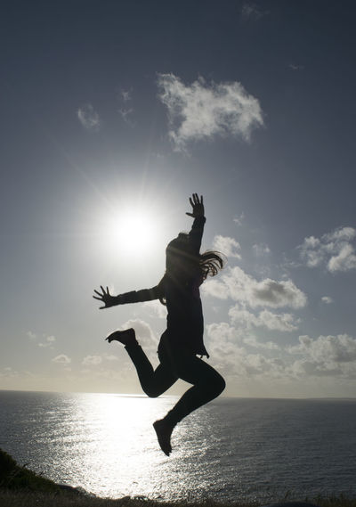 Silhouette woman jumping on beach against sky during sunset