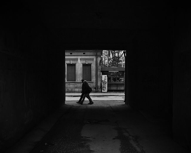 Man and woman walking on street seen from tunnel