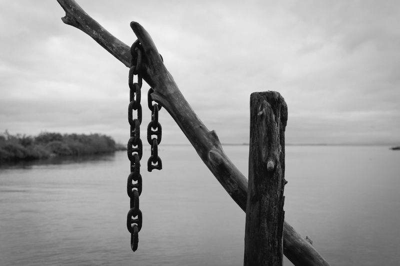 EyeEmNewHere Blackandwhite Water Sky Metal Chain No People Focus On Foreground Sea Hanging Wooden Post Tranquil Scene