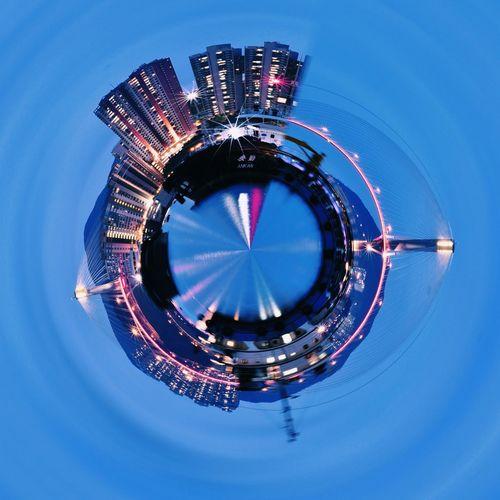 Digital composite image of illuminated buildings against blue sky