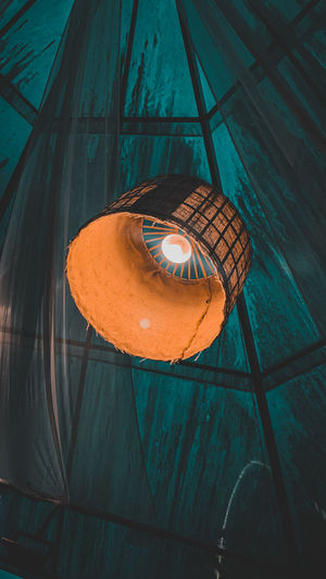 Low angle view of illuminated lantern hanging on wall