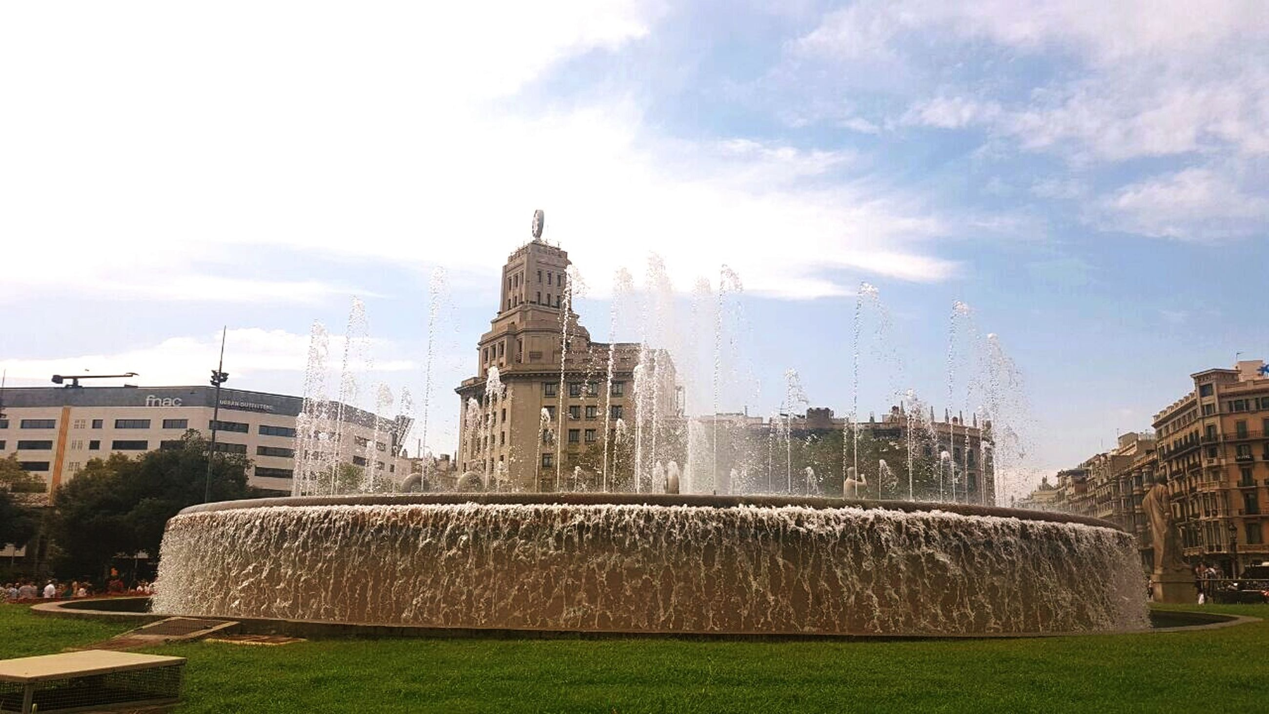 architecture, built structure, motion, building exterior, grass, fountain, spraying, lawn, sky, spray, splashing, dome, lens flare, water, travel destinations, cloud, day, green color, parliament building, sunbeam, facade, outdoors, cloud - sky, sun, growth, history, government building, garden, famous place, the past, arch, government, city life