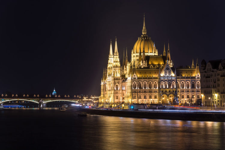 Illuminated Hungarian Parliament Building In City By Danube River At Night