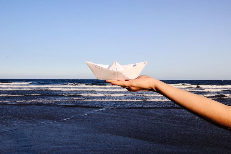 Person holding paper boat against clear sky