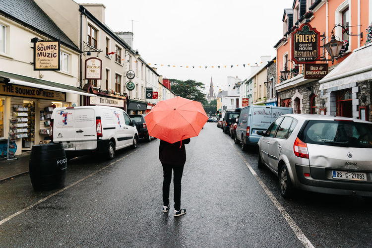 Woman with red umbrella in commercial street in the town of Kenmare in the Wild Atlantic Way of Ireland Ireland Kenmare Red Umbrella Shopping Travel Wild Atlantic Way Woman Architecture Building Exterior Built Structure City City Life Commercial Irish Outdoors Rainy Season Rear View Ring Of Kerry Road Store Storefront Town Travel Destinations Umbrella Village