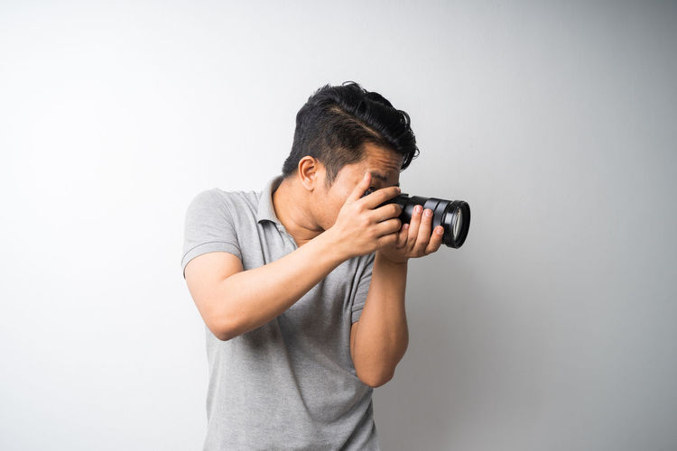Young man photographing against white background