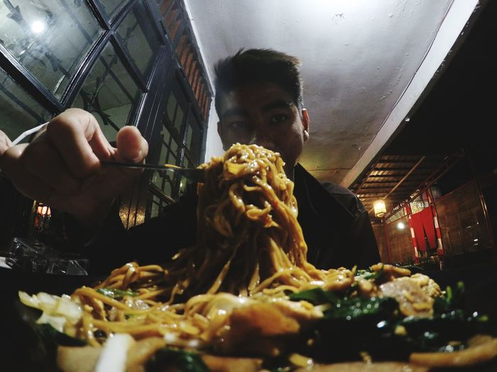 Portrait of man having noodles at restaurant