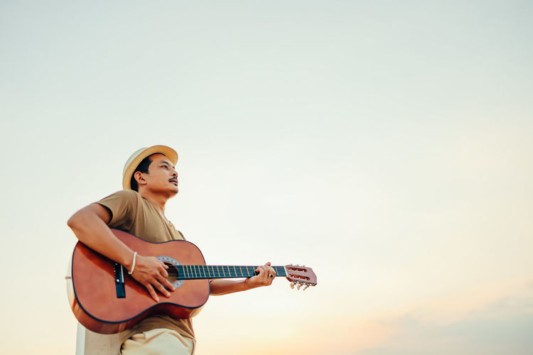 Low angle view of man playing guitar against sky