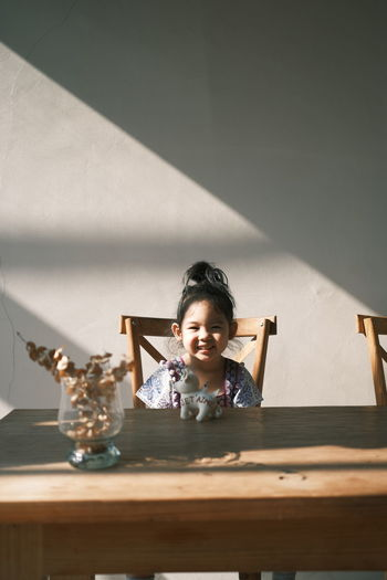Portrait of smiling girl on table