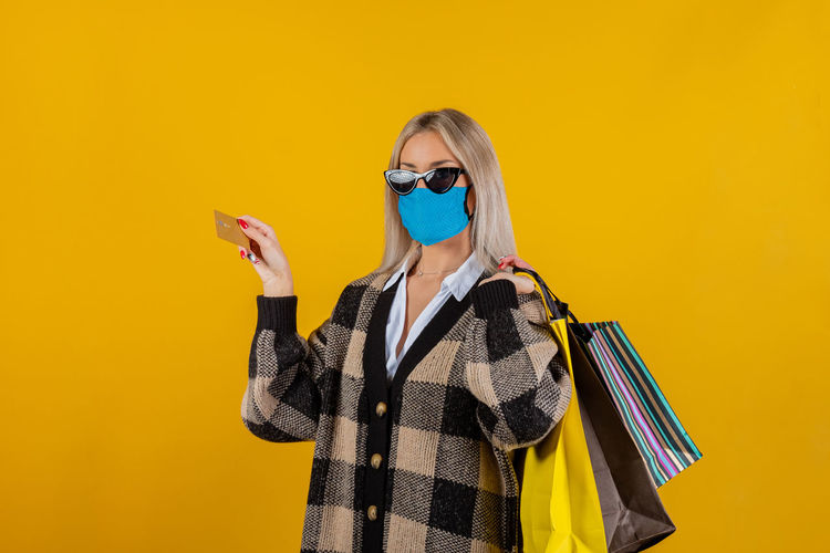 Woman wearing safety gauze mask for prevention from coronavirus, with bags and credit card in hand