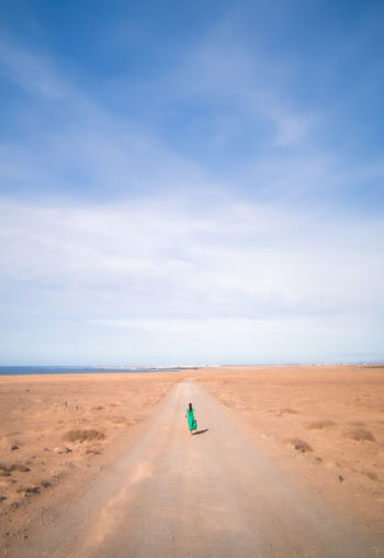 Mid distance view of woman walking on road at desert