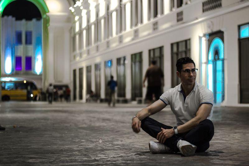 Man sitting on footpath