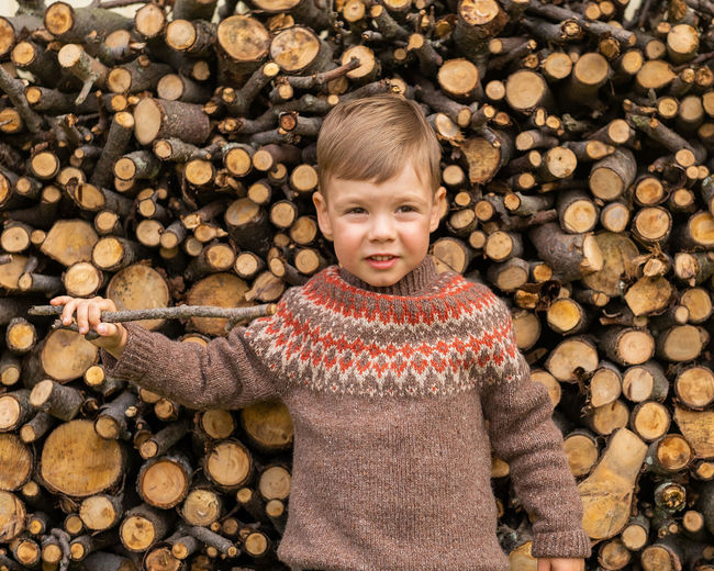 A boy in a lopapeis sweater holds a stick in his hands and stands against the background of firewood