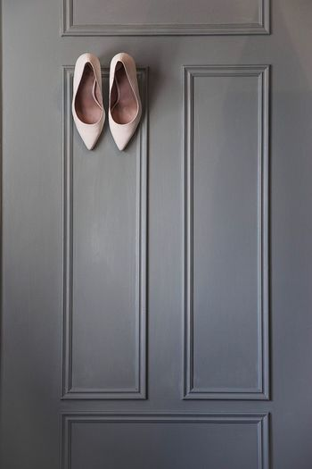 Close-up of high heels hanging on wooden door