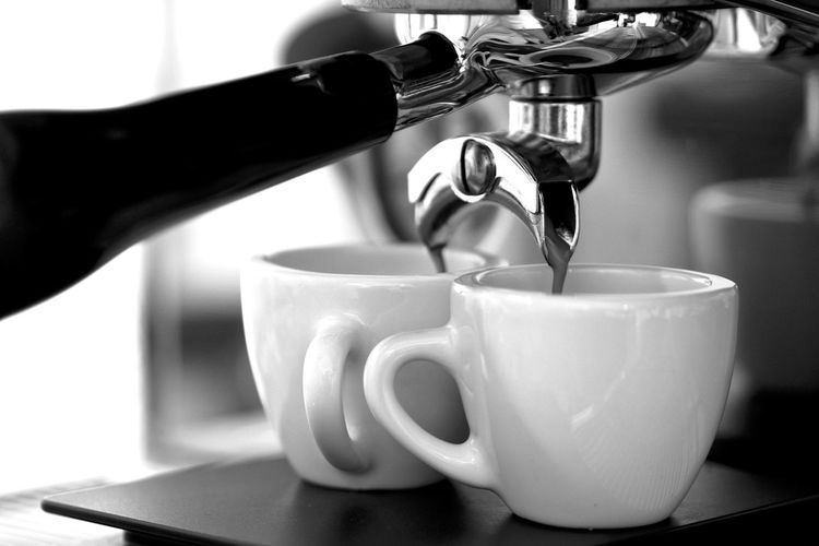 Close-up of coffee pouring in cup in cafe