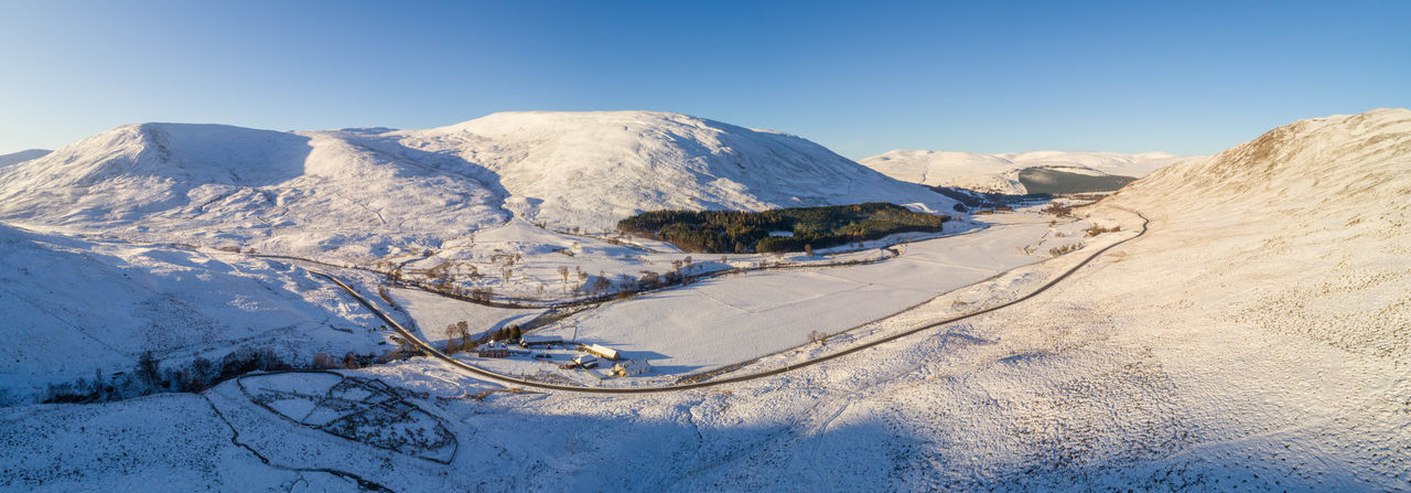 Cairngorms snow road to Braemar Cairngorms National Park Drone  Low Angle View Panoramic Scotland Winter Winter Scene Aerial View Blue Sky Droneshot Highlands Snow Covered Snowcapped Mountain