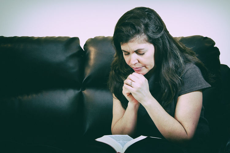 Christian faith: Real life middle age woman praying at home Christian Christianity Devotional Faith Meditation Belief Believe Bible Day Human Hand Indoors  Instagramesque Lifestyles One Person People Prayer Praying Real People Religion Religious  Reliion Sitting
