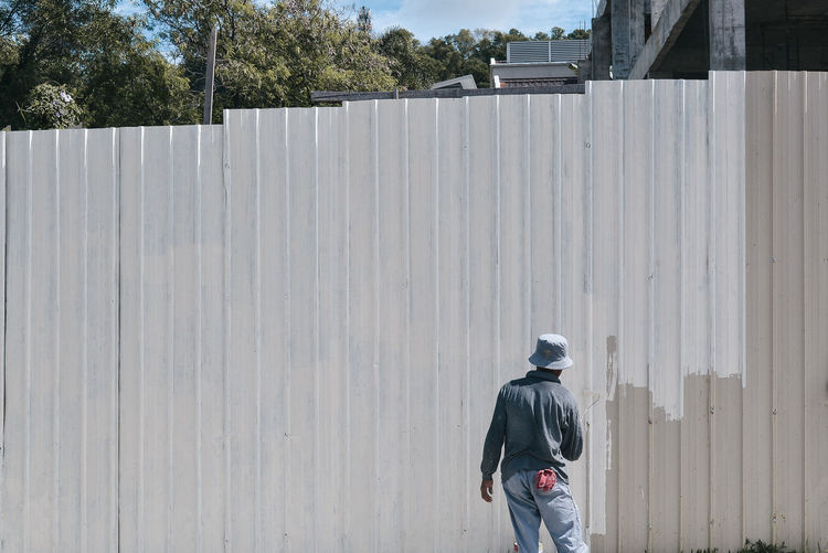 Rear view of man painting wall outdoors