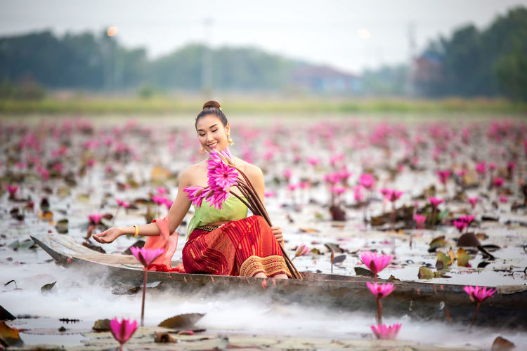 Smiling young woman holding water lilies in boat on lake