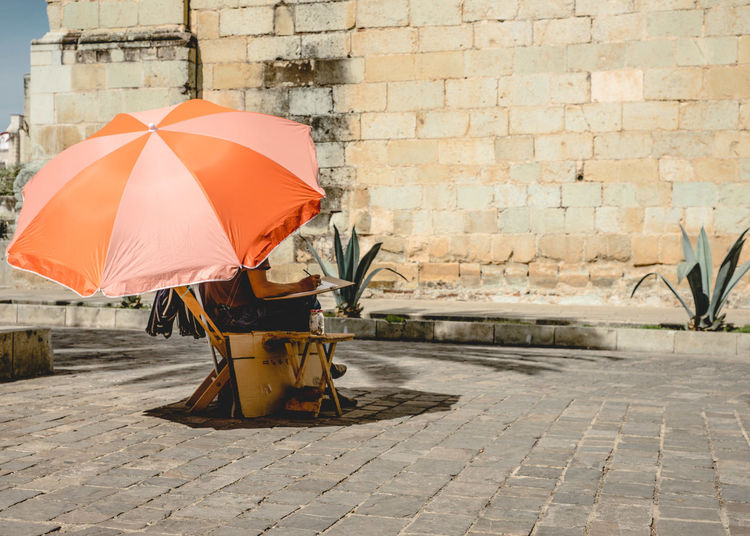 Low section of artist with orange parasol sitting on street against wall