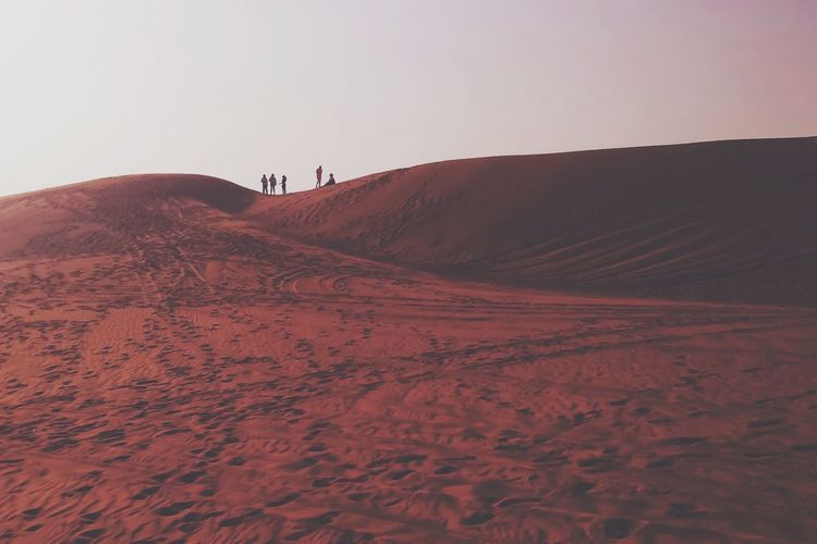 Scenic view of people atop sand dunes