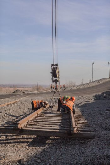 Workers Adjusting Chains On Tracks Against Sky