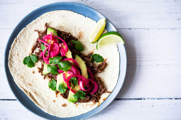 Beef cheek tacos Food And Drink Food Healthy Eating Freshness Wellbeing Ready-to-eat Vegetable Indoors  Close-up No People Meat Garnish Beef Tacos Avocado Cilantro Coriander Lime Tortilla Mexican Food Texmex White Background Onions Pink Color Directly Above