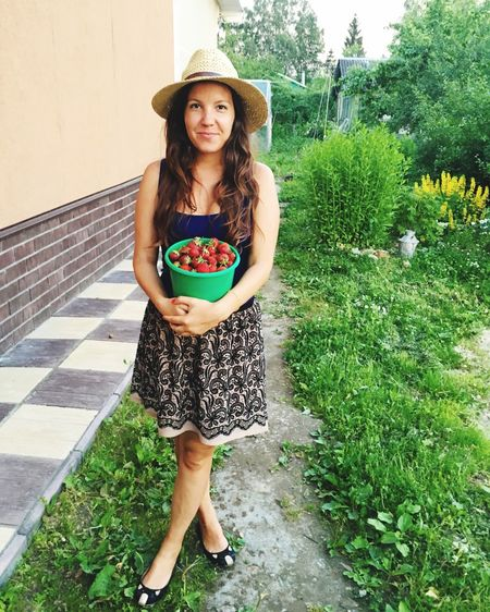 Portrait of young woman holding strawberries in container while standing in yard