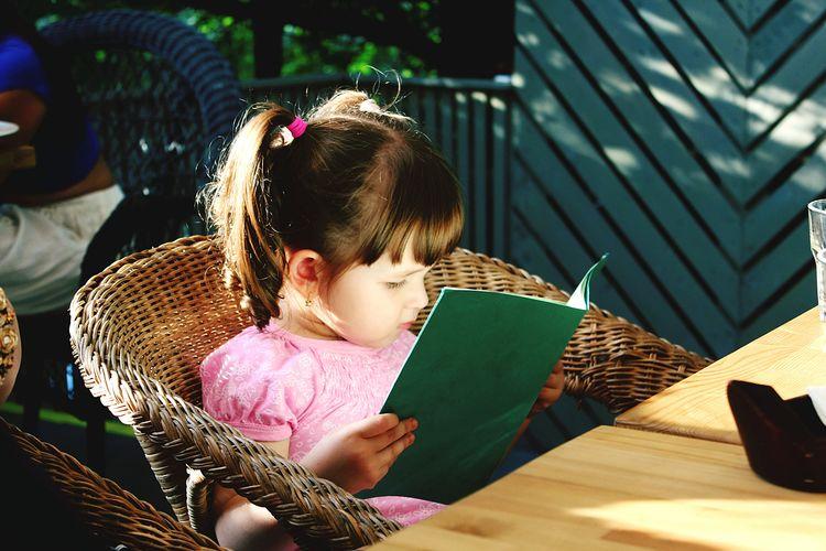 Girl reading menu at restaurant