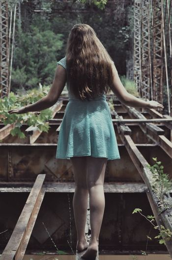Rear view of woman standing on abandoned bridge