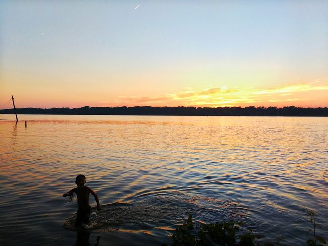 Sunseton the Mississippi River at Sunset Park in Rock Island Illinois . River Golden Sunset Water Swimming Child Boy In Water Carefree Calm