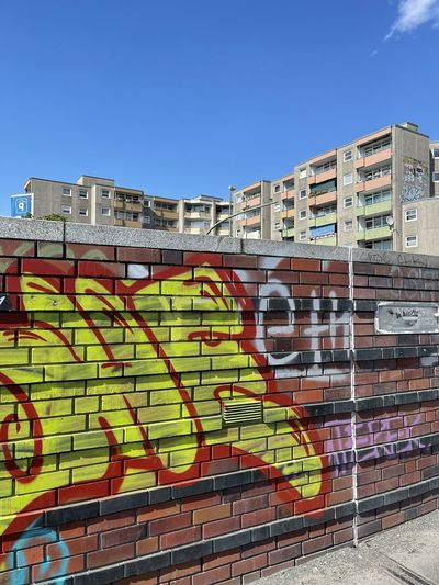 Graffiti on wall against buildings in city