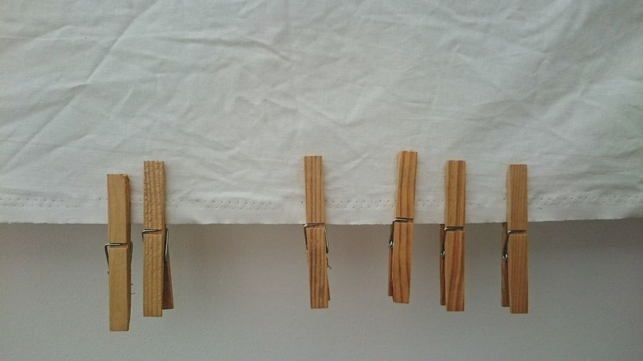 Wooden Clothespins On White Fabric