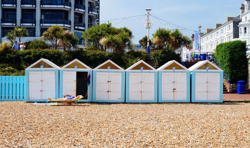 Woman sunbathing by huts at beach