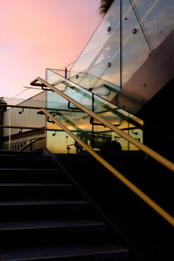 Low angle view of steps and building against sky during sunset