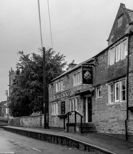 The Artichoke and church, Moulton, Northamptonshire #moulton northamptonshire Architecture Fujfilmxt10 Northamptonshire Monochrome Monochrome Photography Moulton Village Architecture Black And White Church Pubs Northampton Pubs