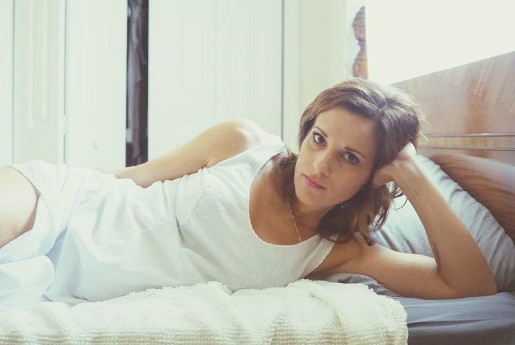 Portrait of young woman relaxing on bed at home