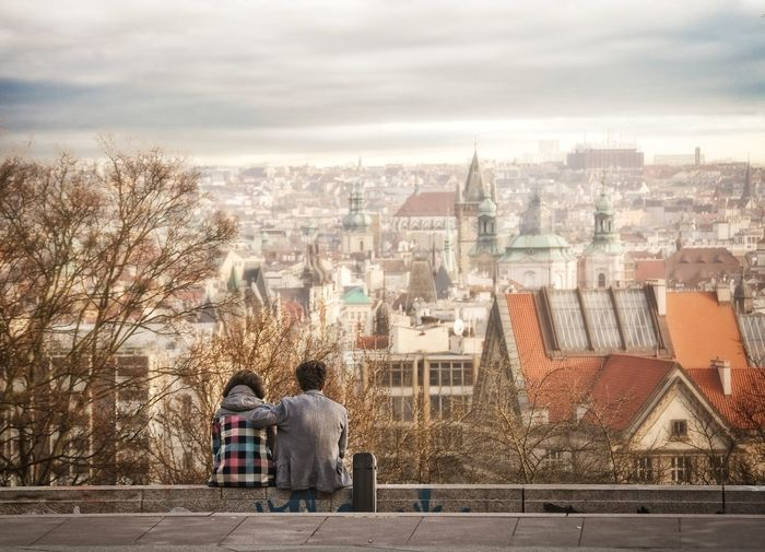 A couple sitting together on a hill and looking at city Architecture City Life Cityscape Cuore Lifestyles Love ♥ Romantic Relationship Romentic Sky The Way Forward Town