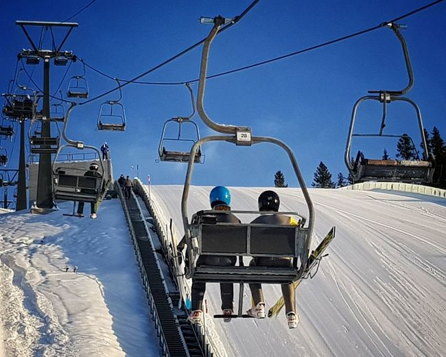 Rear view of ski lift against snowcapped mountain