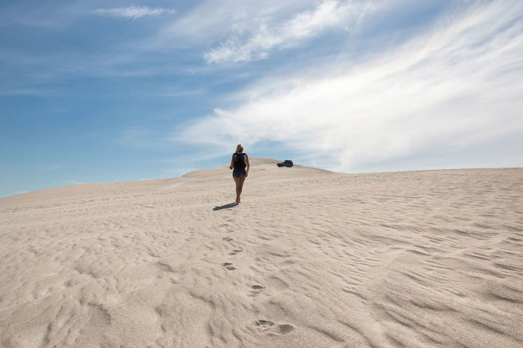 Rear view of man on sand dune
