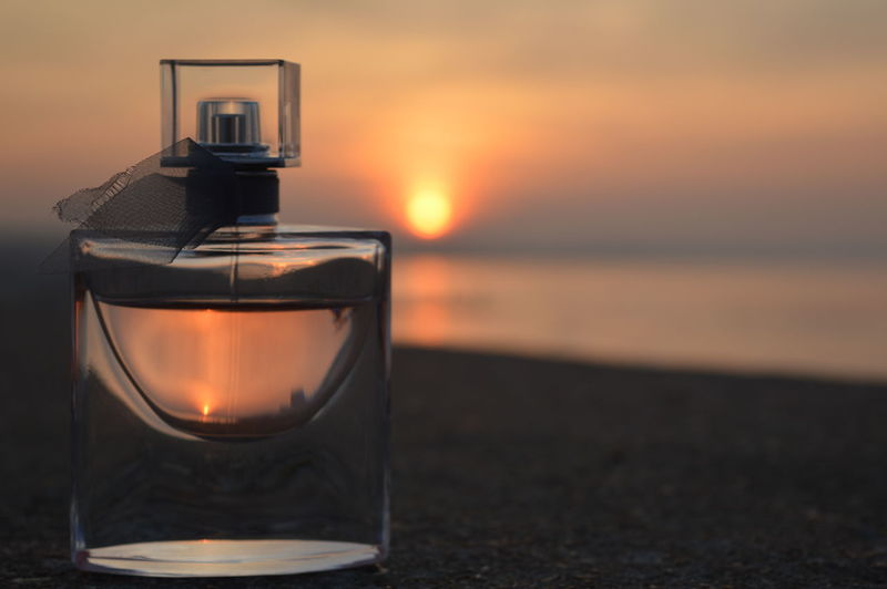 Close-up of perfume bottle at beach against sky during sunset