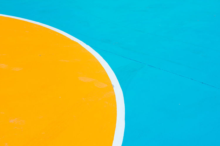 Part of basketball court in colorful Blue Yellow No People Close-up Day High Angle View Pool Swimming Pool Outdoors Geometric Shape Nature Circle Orange Color Shape Still Life Curve Sunlight White Color Semi-circle Full Frame Orange Turquoise Colored