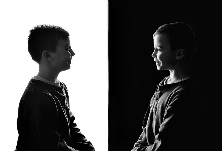 Smiling boys holding hands standing against black and white background