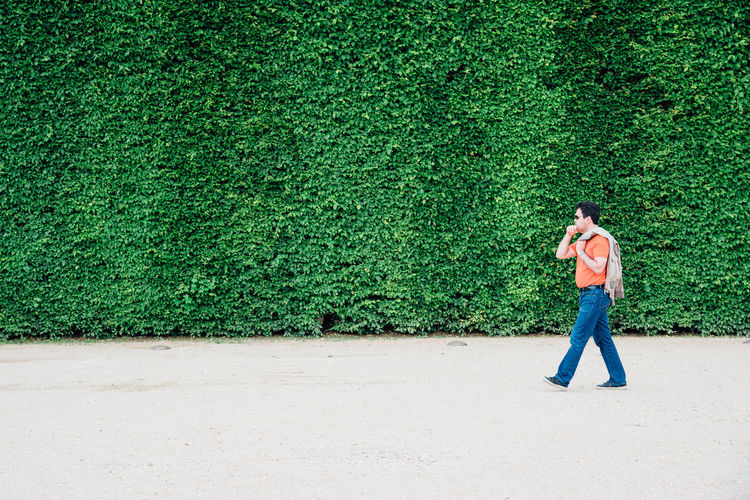 Full Length Side View Of Man Walking By Plants In Park