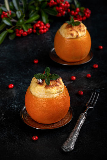 Custard souffle inside orange, on black background, decorated for winter holidays. Black Background Christmas Dessert Dessert Time! Desserts Food And Drink Holiday Orange Souffle Cream Custard Food Food Photography Foodphotography Healthy Eating High Angle View Mint Leaf - Culinary Orange - Fruit Orange Color Sweet Sweet Food Sweets Temptation